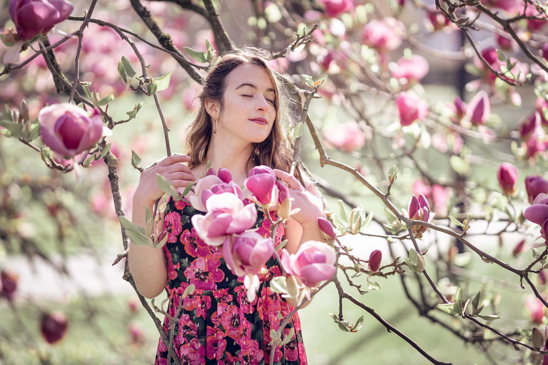 portrait d'une femme rêveuse dans un magnolia fleuri