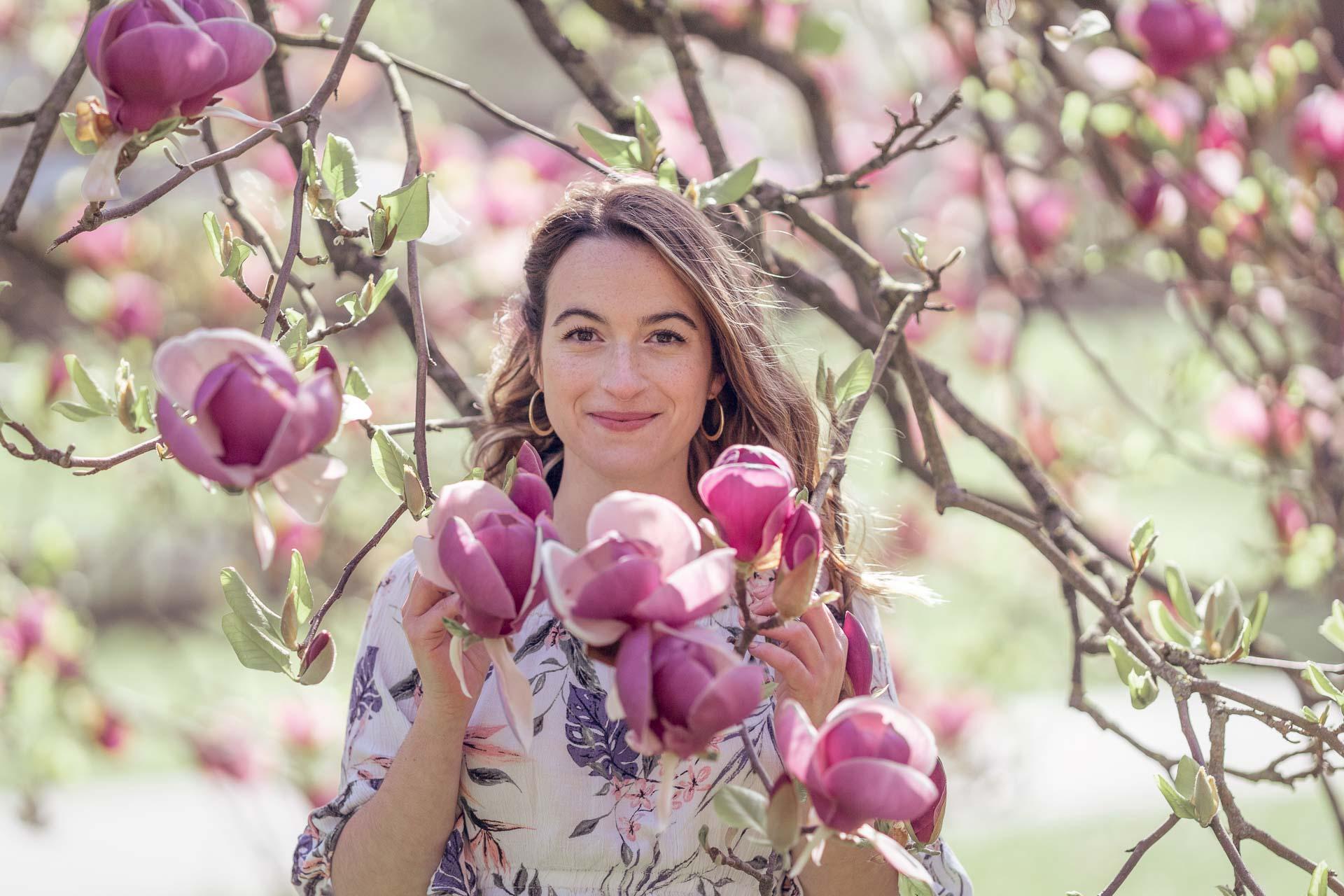 portrait séré d'une femme dans un magnolia en fleurs